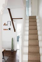 White painted staircase with beige striped carpet