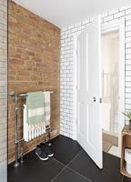 Exposed brick wall and brick style white tiling in modern bathroom