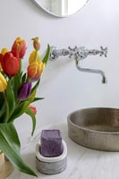 Colorful tulips next to round metal sink