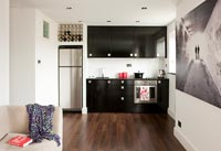 Small black kitchen in open plan studio apartment
