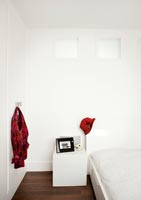 Splashes of red in white modern bedroom
