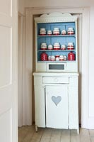 Painted vintage dresser with display of red and white storage jars