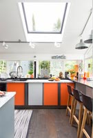 Modern kitchen with grey and orange cabinets and a breakfast bar