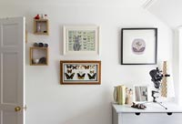 Framed art and butterflies on bedroom wall