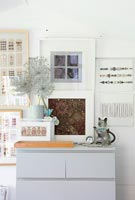 Display of framed pictures and grey chest of drawers