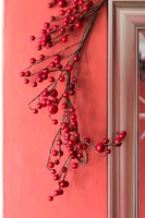 Red berry decoration against red painted wall