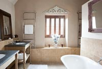 Modern bathroom with bare plaster feature wall