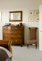 Classic wooden chest of drawers and chair in bedroom