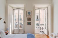 Open French windows in classic bedroom with balcony