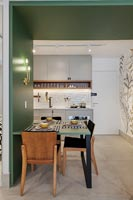 Green wooden frame with built in dining table and view to kitchen