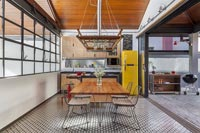 Modern industrial kitchen-diner with bifold doors to barbecue area