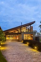 Contemporary house with pitched roof illuminated at night - Brazil