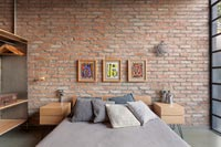 Modern industrial bedroom with exposed brickwork wall