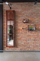 Old mirrored wooden wardrobe door mounted on brick wall