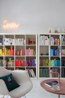 Large bookcases with books arranged by colour and neon art