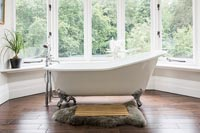 Freestanding bath in bathroom with large windows