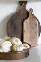 Small white pumpkins and wooden chopping boards