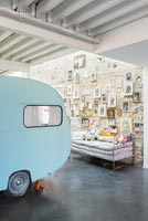 Display of pictures on stone wall and vintage caravan in childrens room