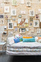 Large stone wall filled with pictures over daybed in childrens room