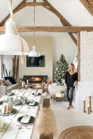 Woman in open plan living space with dining table set for Christmas dinner