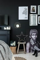 Black painted wall with artwork in modern bedroom