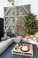 Woman relaxing in living room decorated for Christmas