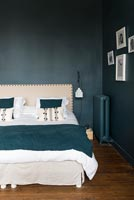 Teal painted walls and matching bedspread in modern bedroom