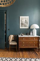 Classic wooden chest of drawers in modern bedroom with teal painted walls