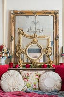 Collection of gilded mirrors on mantelpiece