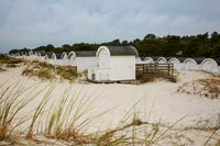 Tiny white wooden cabins along coastal shoreline