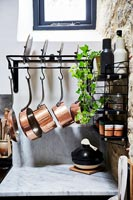 Copper pots on storage rack in modern kitchen