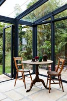 Round table and two wooden chairs in modern conservatory