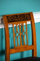 Antique cherry wood dining chair next to dado rail on painted wall