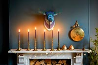 Decorative crocheted trophy head and candles over fireplace