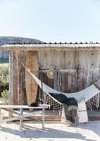 Hammock in rustic wooden shelter on beach