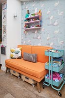Flamingo wallpaper and orange sofa in colourful childrens room