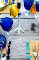 Outdoor wooden table laid for lunch with chicken foot candle holder