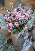 Christmas decoration with dried pink roses and silver sprayed foliage