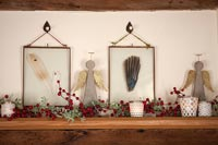 Christmas decorations and framed feathers on shelf