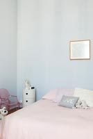 Pale blue walls and pink bedding in childrens room