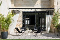 Garden chairs and table on gravel terrace with curtains for shade