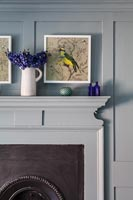 Painting of a bird above fireplace