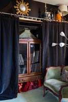 Black wall curtains open to reveal wooden cabinet
