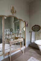 Large mirror and marble console table in classic bathroom