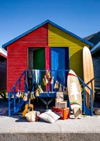 Surfboard and gifts outside colourful beach huts