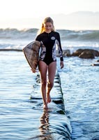 Young woman standing in sea holding a surfboard