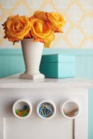 Vase of orange roses on cabinet with stick on storage pots