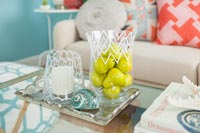 Fruit in glass vase in colourful modern living room