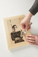 Woman pressing picture to wooden frame using a spoon