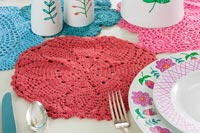 Painted plates with folk art motifs on dining table with crocheted mats